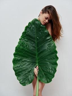 Rothaarige frau bedeckt nackten körper mit hellem hintergrund aus palmblättern