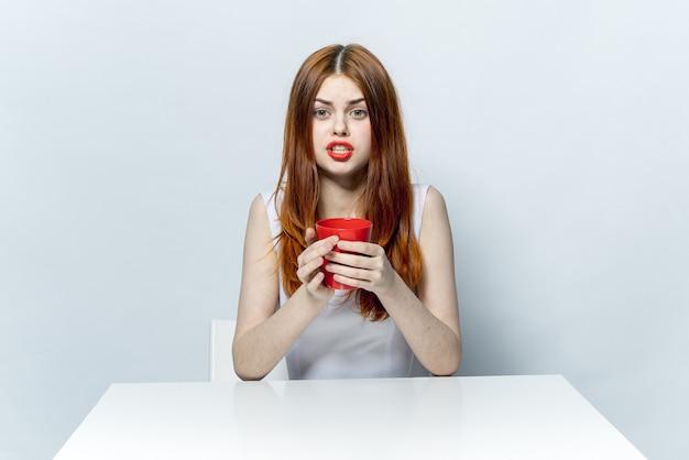 Rothaarige frau, die am tisch mit einer tasse getränkeentspannungsgefühle sitzt