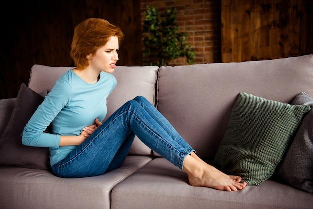 Rothaarige frau, die auf dem sofa zu hause aufwirft