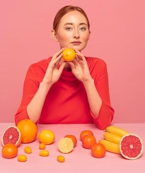 Rothaarige frau, die eine orange hält