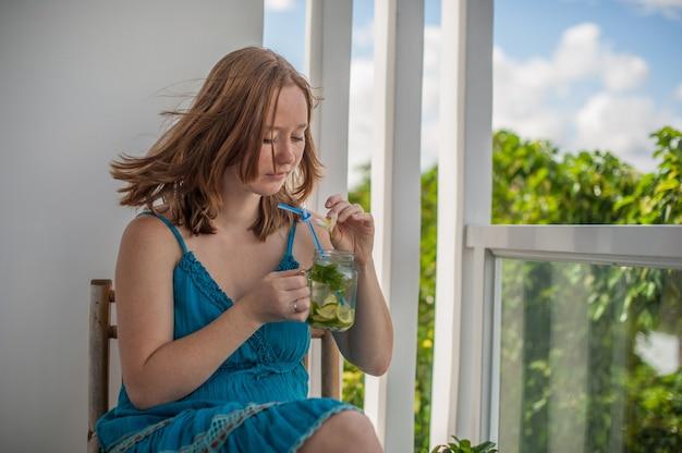 Rothaarige frau, die einen mojito auf der terrasse trinkt