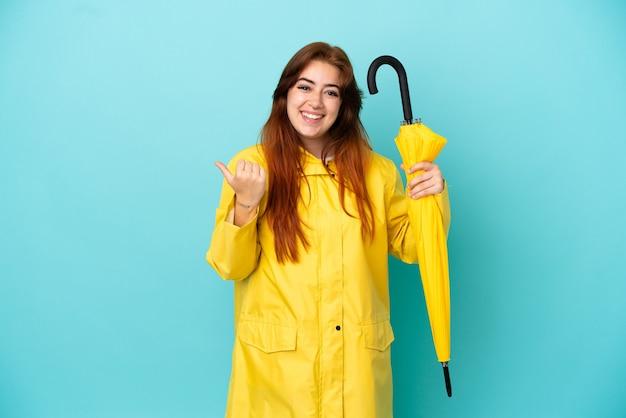 Rothaarige frau, die einen regenschirm isoliert auf blauem hintergrund hält und auf die seite zeigt, um ein produkt zu präsentieren