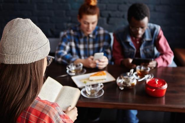 Rothaarige frau, die online-bestellung beim einkaufen über das internet am mobiltelefon beim mittagessen im modernen café-innenraum mit freunden macht. selektiver fokus auf nicht erkennbare frau, die buch liest
