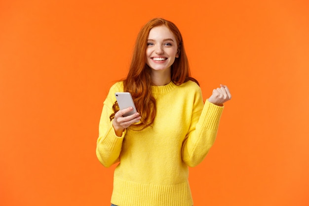 Rothaarige frau, die smartphone, faustpumpe im triumph oder in der feier hält und im spiel gewinnt