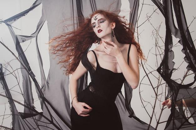 Rothaarige frau eine hexe wartet auf halloween. rothaarige schwarze magierin. mystische zauberei, magische reize
