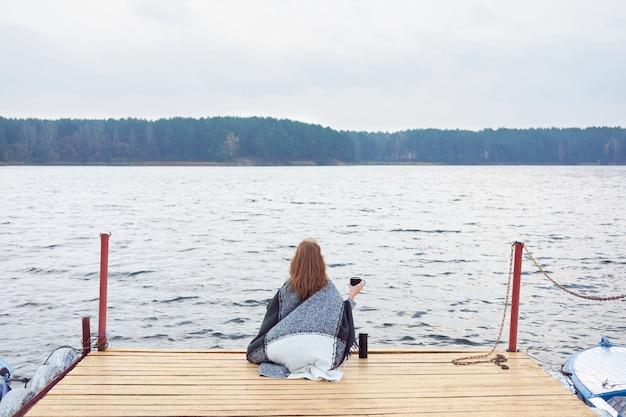 Rothaarige frau, eingewickelt in eine karierte decke, sitzt auf dem pier des sees und trinkt kaffee aus der thermoskanne