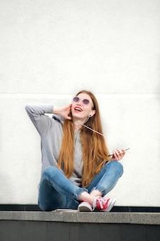 Rothaarige frau gekleidet in kapuzenpulli, jeans und roten turnschuhen, mit roten lippenstift gemalten lippen, die musik im smartphone im sonnigen sommertag hören und spaß haben
