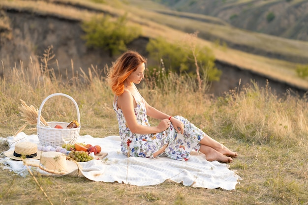 Rothaarige frau genießt den sonnenuntergang in der natur. picknick auf dem feld.