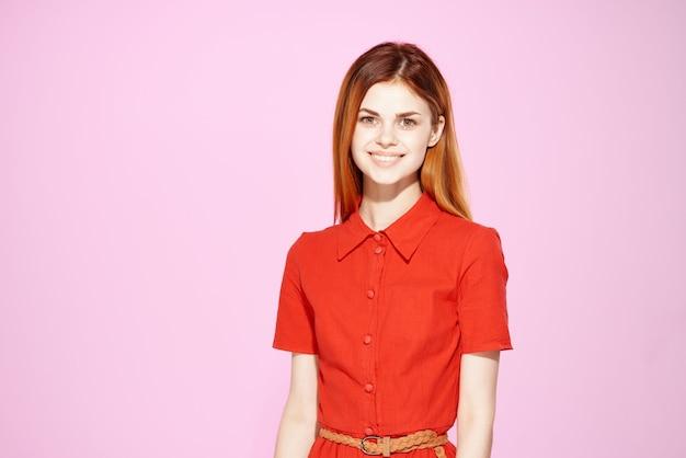 Rothaarige frau im eleganten rosa hintergrund der roten kleidermode