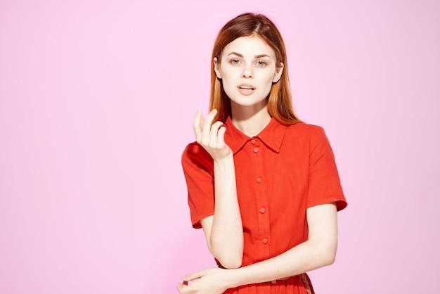 Rothaarige frau im roten kleid handgesten luxus rosa hintergrund
