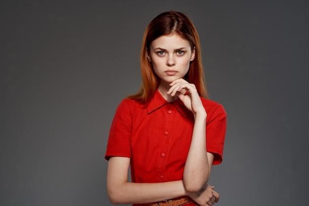 Rothaarige frau im roten kleid posiert attraktiven blick isolierten hintergrund