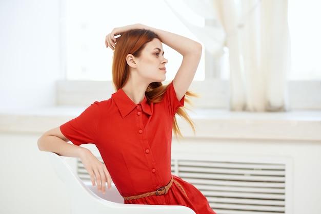 Rothaarige frau im roten kleid posiert auf einer stuhlmode