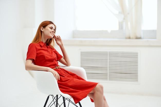Rothaarige frau im roten kleid sitzt in der nähe der fenstermode