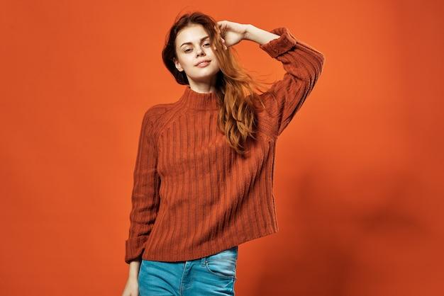 Rothaarige frau im roten pullover attraktiven look glamour studio modische kleidung.