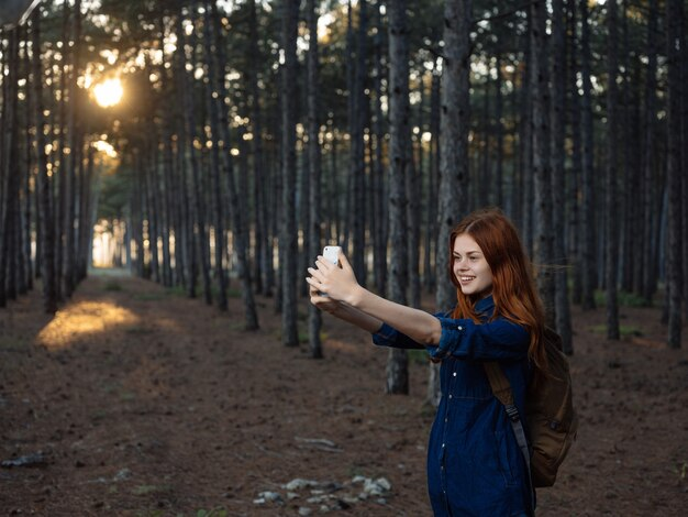 Rothaarige frau in der waldnatur-reisewegfreiheit