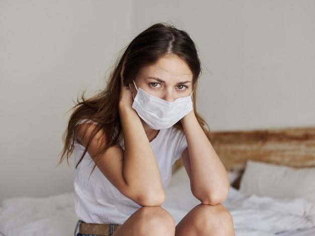 Rothaarige frau in medizinischer maske, die in einem isolierten raum auf dem bett sitzt