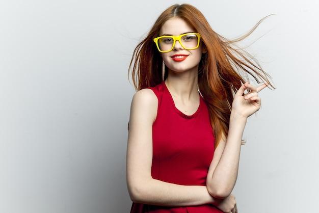 Rothaarige frau in rotem kleid und gelber brille, weiß
