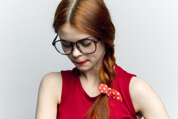Rothaarige frau in rotem kleid und schwarzer brille