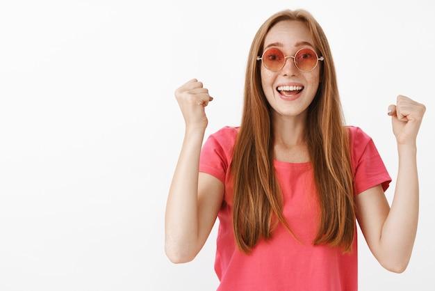 Rothaarige frau jubelt und hebt die fäuste hoch in unterstützender bewegung, lächelt freudig und schreit weiter, um das selbstvertrauen zu stärken
