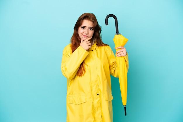 Rothaarige frau mit einem regenschirm isoliert auf blauem hintergrund denken