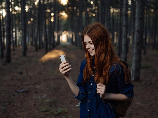 Rothaarige frau mit einem telefon in den händen im wald spaßreisen