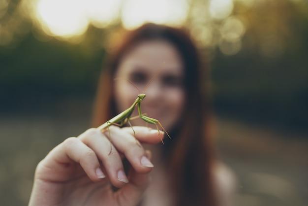 Rothaarige frau mit einer gottesanbeterin in der hand naturspaziergang. foto in hoher qualität