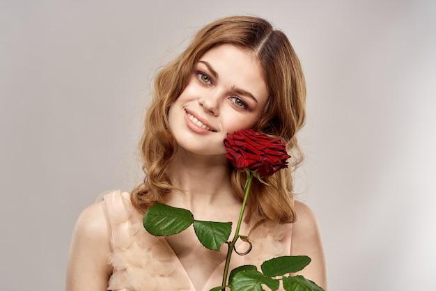 Rothaarige frau mit einer rose in ihren händen auf einem hellen hintergrund emotionen modellporträt nahaufnahme.