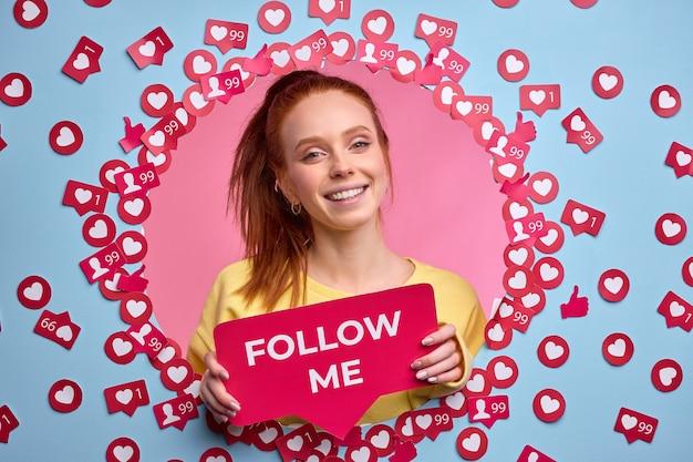 Rothaarige frau mit follow me-zeichen, bitte darum, im internet aktiver zu sein, likes und nachrichten zu senden