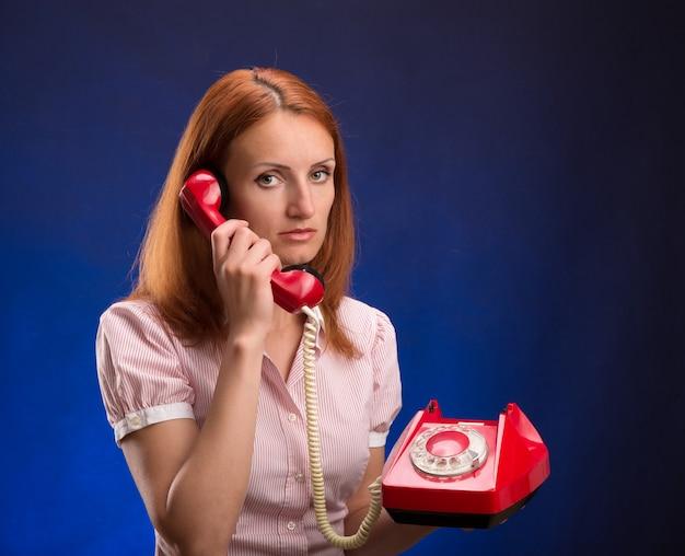 Rothaarige frau mit rotem telefon
