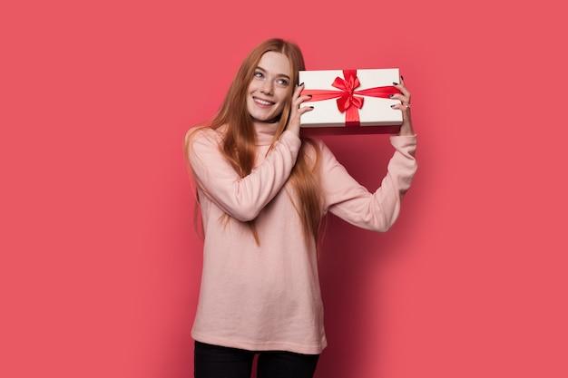 Rothaarige frau mit sommersprossen schüttelt ein geschenk und lächelt auf einer roten wand im studio