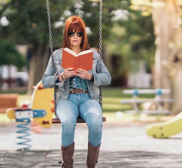 Rothaarige frau mit sonnenbrille, die ein buch liest, während sie an einem sonnigen tag auf einer schaukel in einem park sitzt