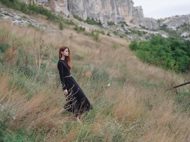 Rothaarige frau schwarzes kleid zu fuß berge freiheit