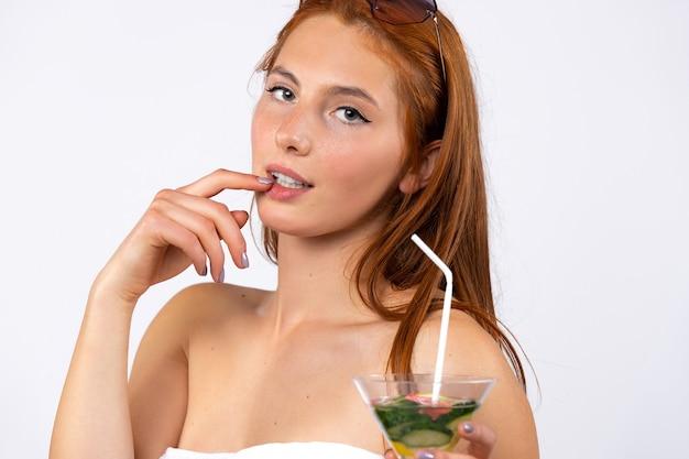 Rothaarige frau sexy posiert mit einem cocktail auf einem weißen wand spa und schönheitskonzept