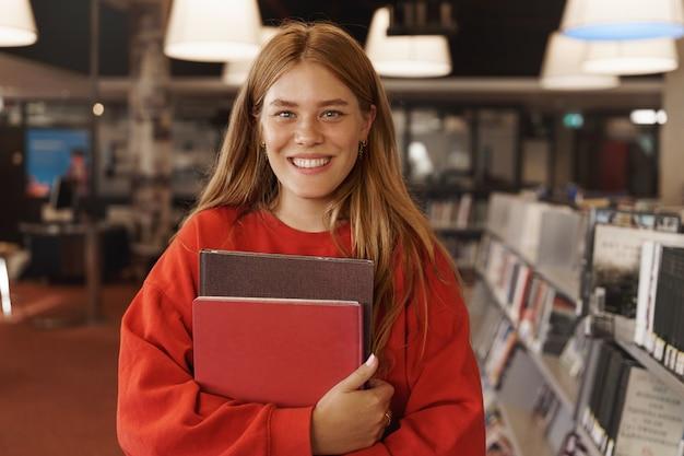 Rothaarige frau studiert, hält bücher im buchladen und lächelt.