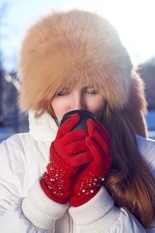 Rothaarige frau trägt fuchspelzmütze und weiße jacke und trinkt kaffee, um in den kalten wintertag zu gehen