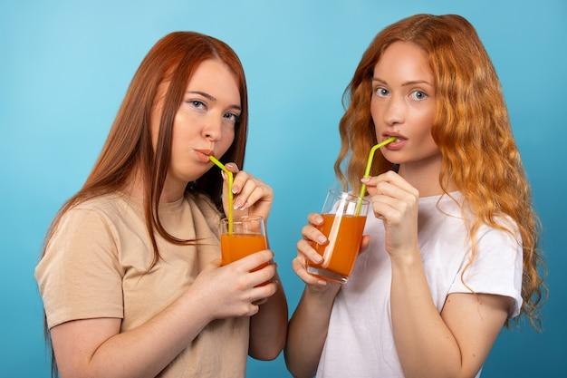 Rothaarige frauen trinken orangensaft aus gelben strohhalmen an der blauen wand