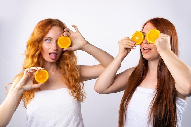 Rothaarige freundinnen haben spaß und posieren mit orangenscheiben. gesundes essen, spa und schönheit, vitamine und glückskonzept. foto auf weißer wand.