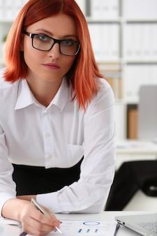 Rothaarige geschäftsfrau, die am büroarbeitsplatzporträt sitzt