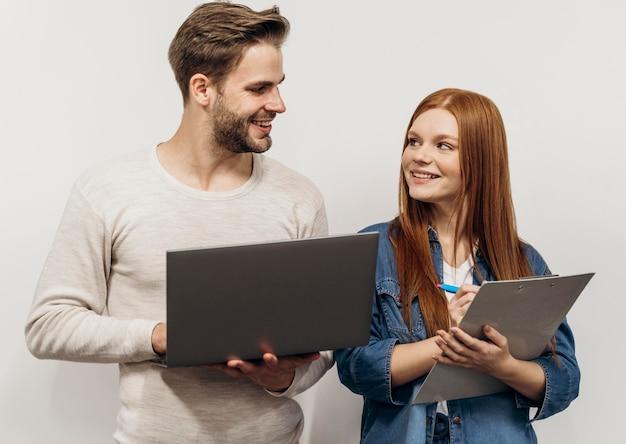 Rothaarige geschäftsfrau, die mit ihrem kollegen an einem laptop arbeitet