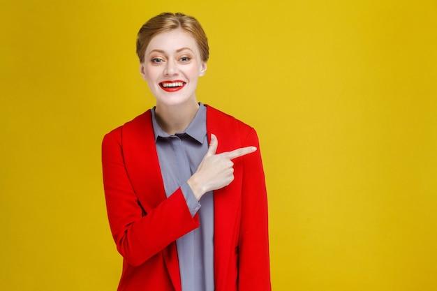 Rothaarige geschäftsfrau im roten anzug, die am kopienraum zeigt