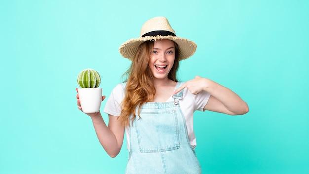 Rothaarige hübsche bäuerin, die sich glücklich fühlt und auf sich selbst zeigt, mit einem aufgeregten und hält einen kaktus