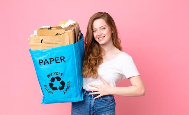 Rothaarige hübsche frau, die laut über einen urkomischen witz lacht und eine recyclingpapiertüte hält