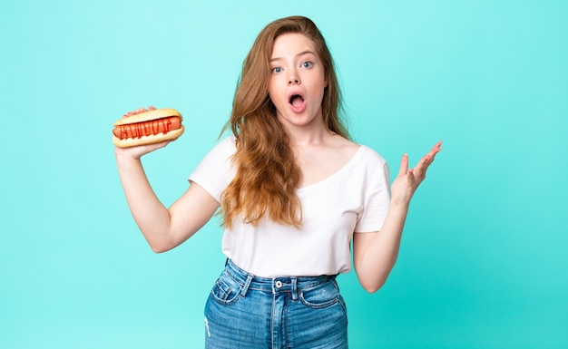 Rothaarige hübsche frau, die sich extrem schockiert und überrascht fühlt und einen hot dog hält