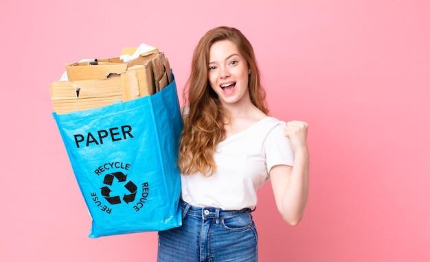 Rothaarige hübsche frau, die sich schockiert fühlt, lacht und den erfolg feiert und eine recyclingpapiertüte hält
