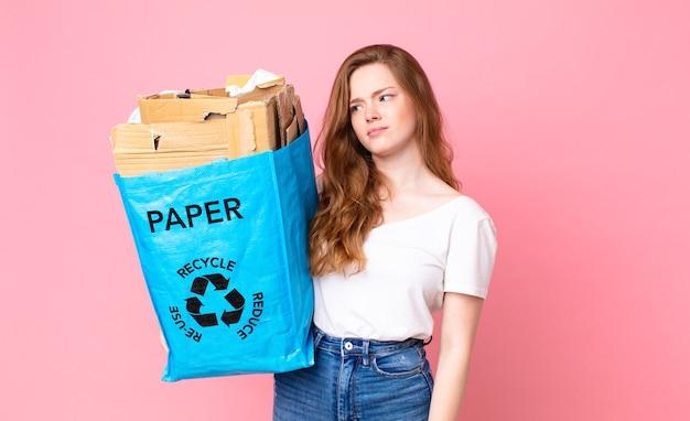 Rothaarige hübsche frau, die sich traurig, verärgert oder wütend fühlt und zur seite schaut und eine recyclingpapiertüte hält