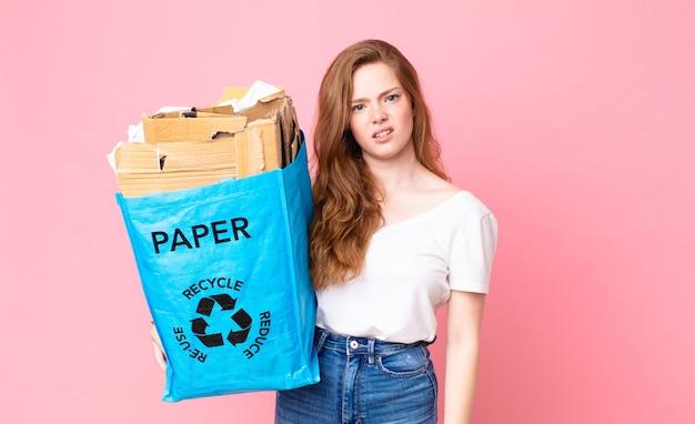 Rothaarige hübsche frau, die sich verwirrt und verwirrt fühlt und eine recyclingpapiertüte hält
