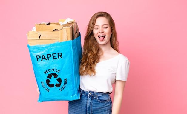 Rothaarige hübsche frau mit fröhlicher und rebellischer haltung, die scherzt und die zunge herausstreckt und eine recyclingpapiertüte hält