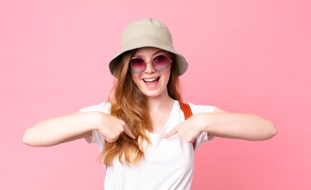 Rothaarige hübsche touristin, die sich glücklich fühlt und mit einem aufgeregten auf sich selbst zeigt
