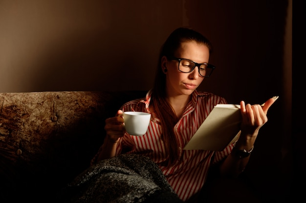 Rothaarige ingwermädchen in abgestreiftem hemdlesebuch, trinkendem kaffee, liegend auf dem sofa und dem lächeln