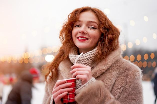 Rothaarige junge frau, die weihnachtsfeiertag winterferienzeit steht